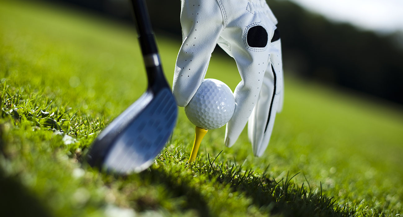 Closeup of a hand with golf glove when placing a golf ball on the grass