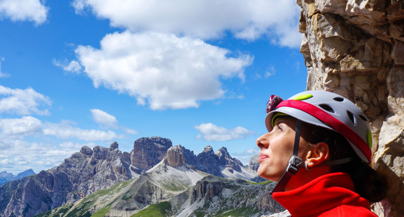 Climber with helmet enjoying the view and the sun high up in the mountains