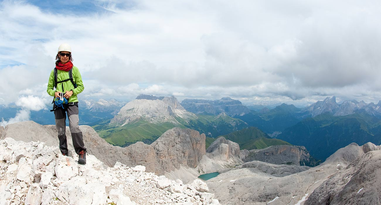 Alpine climber on the top of a crested mountain in Alta Badia