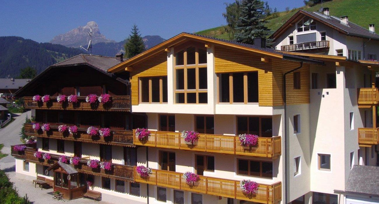 Hotel Alcialc in La Villa in Alta Badia from the outside with geraniums on the balconies