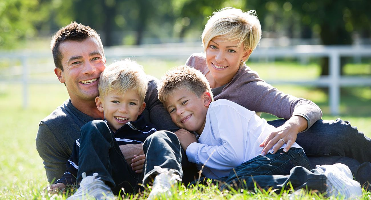 Smiling family while cuddling on a meadow