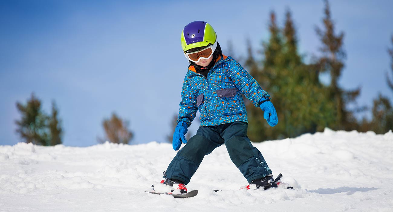 Little child with helmet snowplow-skiing on a slope