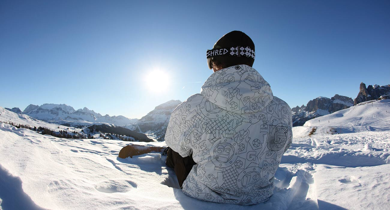 Snowboarder sitting in the snow and enjoying the bright blue sky and the sun