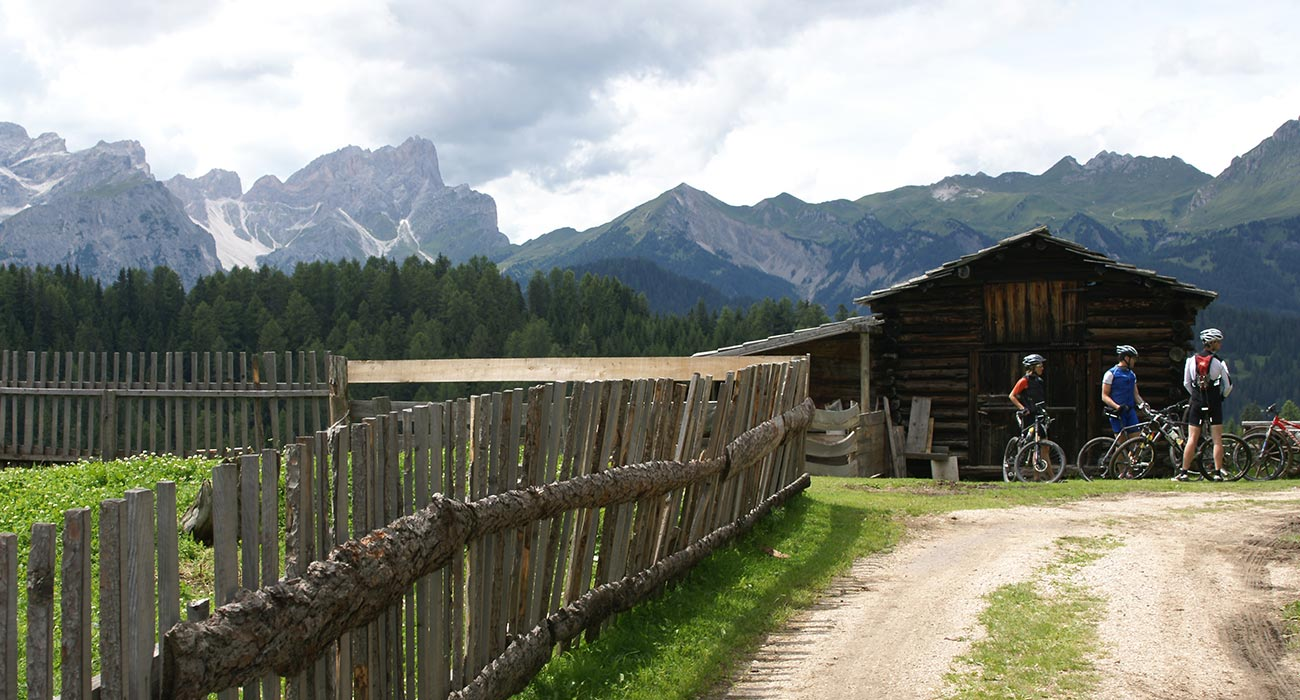 Mountain bikers take a rest on a small wooden hut with a wooden fence in the mountains of Alta Badia